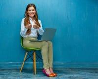 Femme avec l'ordinateur portable se reposant sur la chaise montrant le pouce  Image libre de droits