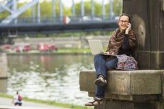 Femme avec l'ordinateur portable se reposant sur le remblai de la rivière dans la vieille ville parlant à un téléphone portable Photo stock