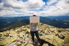 Femme avec l'ordinateur portable se tenant sur une pierre Photos libres de droits