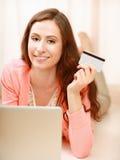 Femme avec l'ordinateur portable se trouvant sur le plancher et tenant a Image stock