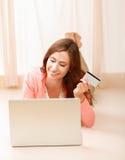 Femme avec l'ordinateur portable se trouvant sur le plancher et tenant a Photos stock