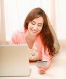 Femme avec l'ordinateur portable se trouvant sur le plancher et tenant a Photos libres de droits