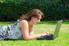 Femme avec l'ordinateur portable sur l'herbe verte Image libre de droits