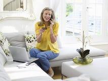 Femme avec l'ordinateur portable utilisant la carte de crédit et le téléphone Images stock