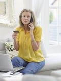 Femme avec l'ordinateur portable utilisant la carte de crédit et le téléphone Photographie stock libre de droits