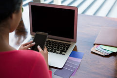 Femme avec l'ordinateur portable utilisant le téléphone photo libre de droits