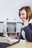 Femme avec l'ordinateur portatif au téléphone photos stock