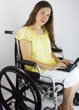 Femme avec l'ordinateur portatif dans le fauteuil roulant Photo libre de droits