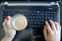 Femme avec l'ordinateur portatif et le café Photo stock