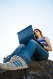 Femme avec l'ordinateur portatif et le ciel bleu Photos libres de droits