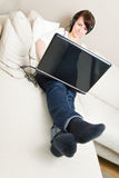Femme avec l'ordinateur portatif et les écouteurs Photographie stock libre de droits