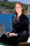 Femme avec l'ordinateur portatif près de la mer Photo libre de droits