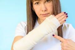 Femme avec l'os de bras cassé dans la fonte, main plâtrée sur le fond bleu images stock