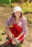 Femme avec l'outil de jardinage fonctionnant dans le jardin Image libre de droits