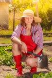 Femme avec l'outil de jardinage fonctionnant dans le jardin Photos stock