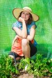 Femme avec l'outil de jardinage fonctionnant en serre chaude Photographie stock
