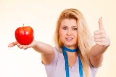Femme avec la bande de mesure autour du cou tenant la pomme Images stock