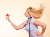 Femme avec la bande de mesure tenant le petit gâteau doux Photo stock