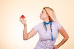 Femme avec la bande de mesure tenant le petit gâteau doux Photo libre de droits