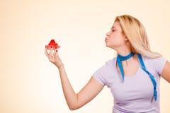 Femme avec la bande de mesure tenant le petit gâteau doux Photographie stock