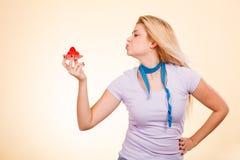 Femme avec la bande de mesure tenant le petit gâteau doux Photographie stock libre de droits