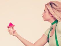 Femme avec la bande de mesure tenant le petit gâteau doux Photos stock