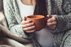 Femme avec la belle manucure tenant une tasse orange de cacao Photo stock