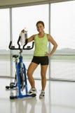 Femme avec la bicyclette d'exercice. Image stock