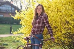 Femme avec la bicyclette de vintage en parc Image stock