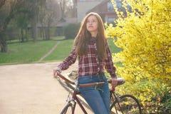 Femme avec la bicyclette de vintage en parc Images libres de droits