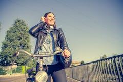 Femme avec la bicyclette marchant dehors Image stock