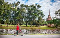 Femme avec la bicyclette près du temple en Thaïlande image libre de droits