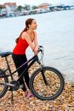 Femme avec la bicyclette sur la plage Photo stock