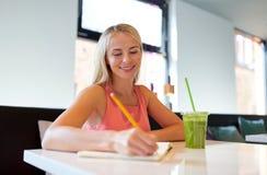 Femme avec la boisson écrivant au carnet au restaurant photos libres de droits