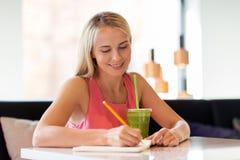 Femme avec la boisson écrivant au carnet au restaurant image stock
