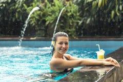 Femme avec la boisson de fuit dans la piscine photos libres de droits