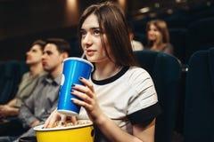 Femme avec la boisson et le maïs éclaté se reposant dans le cinéma images stock