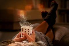 Femme avec la boisson se trouvant sur le sofa photos libres de droits