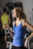 Femme avec la bouteille d'eau regardant loin le gymnase Photographie stock libre de droits