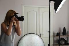 Femme avec la caméra professionnelle dans le studio de photo photo libre de droits