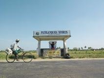 Femme avec la carte à l'arrêt d'autobus comme homme sur des passages de bicyclette par Photographie stock