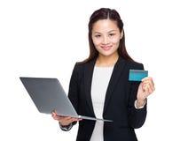 Femme avec la carte de crédit d'ordinateur portable Images stock