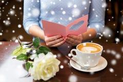 Femme avec la carte de voeux de lecture de café et de fleur Photos stock