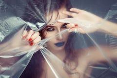 Femme avec la cellophane scrutante de maquillage créatif d'oeil images libres de droits