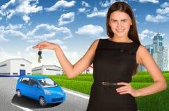 Femme avec la clé de voiture à disposition Petite automobile dessus photographie stock libre de droits