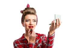 Femme avec la coiffure de goupille- tenant le miroir, appliquant lipstic rouge photos libres de droits