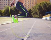 Femme avec la corde à sauter Belle jeune femme avec un RO sautant photo libre de droits