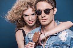 Femme avec la crème glacée étreignant l'homme sur le bleu Photo libre de droits