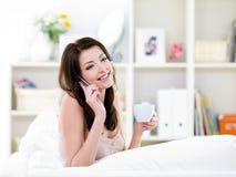Femme avec la cuvette parlant par le téléphone portable Photographie stock
