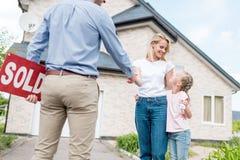 femme avec la fille achetant la nouvelle maison et serrant la main de l'agent immobilier masculin avec le signe vendu images stock
